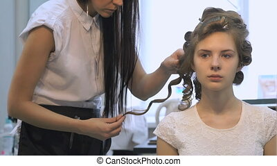 Professional barber makes hairstyle for a girl -...