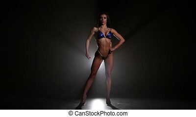 Young sporty woman posing against in bikini on black. Slow...