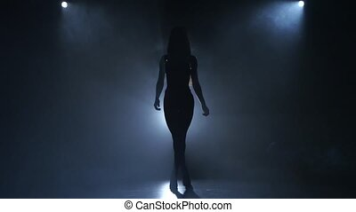 Silhouette bodybuilding girl posing on blue smoke. Bulky...