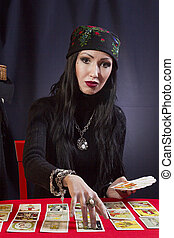 Sorceress wonders by Tarot cards on a black background
