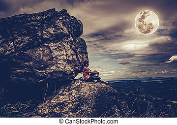 Woman sitting on boulders, sky with cloudy and full moon....