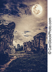 Boulders against sky with clouds and beautiful full moon at...