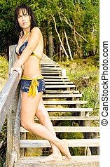 Sensual brunette in a swimming suit on a wooden stair