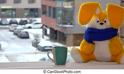 Yellow toy bunny with tea cup sitting by window in winter. Snowflakes falling.