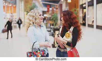 two women talking in the mall. shopping theme