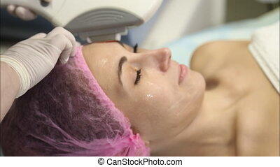 Young woman doing cosmetology laser therapy close-up