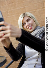 Woman Making Faces While Taking Selfie At Outdoor Cafe -...