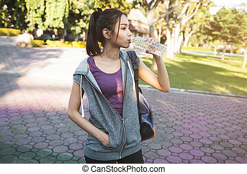 Portrait of young beautiful woman in sport wearing drinking...