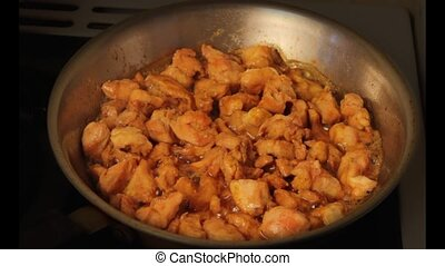 Close-up of pieces of spicy curried chicken frying in oil in...