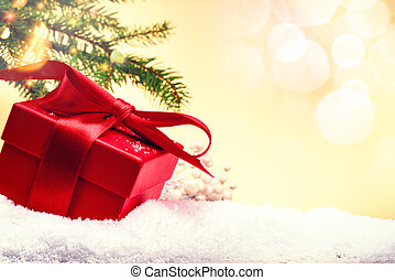 Christmas holiday setting with present in red box over snow....