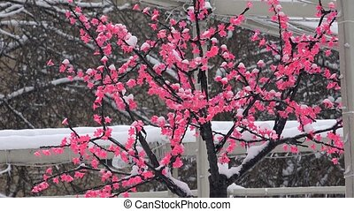 artificial bush flower blooms covered with snow. Snowflakes...