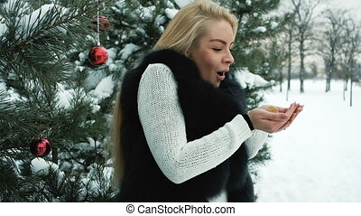 Smiling woman blowing snow from hands in frosty winter in pine fores