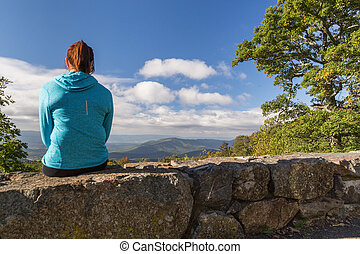 Woman looking down on the Blue Ridge Mountains