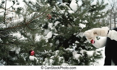 Woman decorates snowy fir-tree with red Christmas toy outdoors