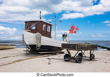 A fishing boat on shore of the Baltic Sea in Koserow,...
