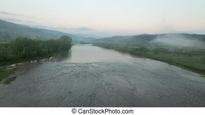 The flow of the river in hilly terrain. Aerial view - Calm...