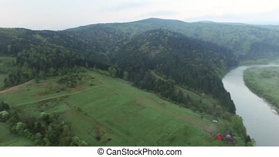 Panoramic shooting high above the ground wooded hills and...