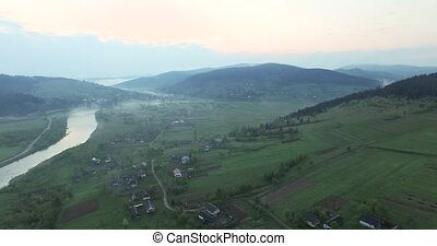 Village on a hilly area on the river bank - Village on a...