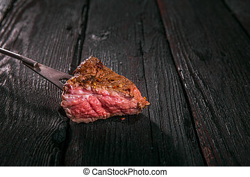 grilled meat. impale a piece of steak on a fork.