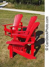 rote Holzgartenstühle auf einer Wiese