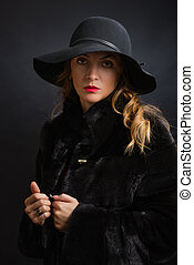 The beautiful young girl in a black hat with wide fields and...