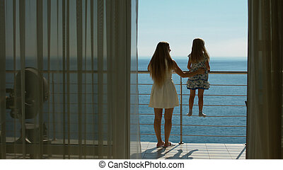 Mom and daughter go to the balcony with the sea view from the guest room