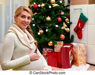 happy pregnant woman sitting on floor and touching her belly over christmas tree background