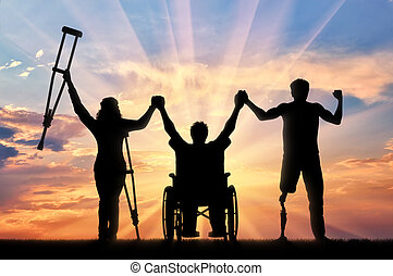 Disabled people holding hands on sunset background