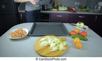 Girl chef pouring oil in the baking sheet, and spreads over...