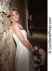 Wedding in a grunge barn - Bride in white posing against a...