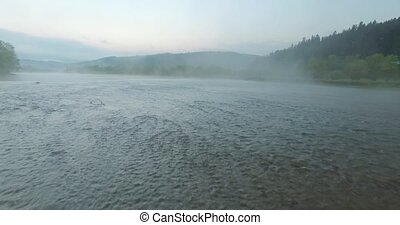Shallow waters of the river in valley of rolling hills -...