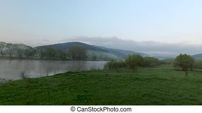 Aerial view. River bank in the hills of the valley - Grassy...