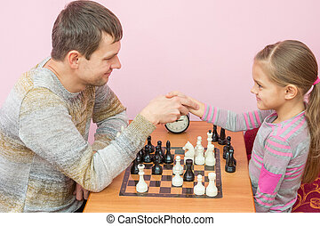 Dad and daughter shook hands, playing a game of chess
