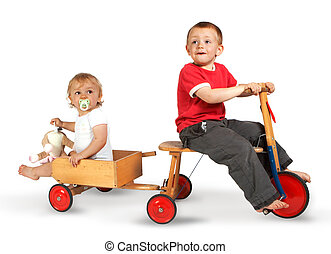 Tricycle - Little boy on a tricycle with his sister in a...