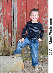 smiling boy by red barn - cute smiling Caucasian boy by...
