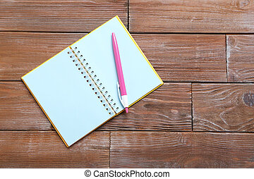 Notebook with pen on brown wooden table