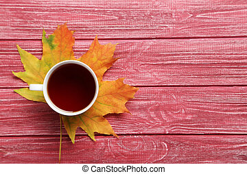 Autumn leaf with cup of tea on red wooden table