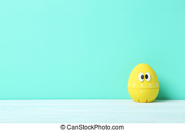 Yellow egg timer with googly eyes on a green background