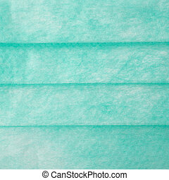 Green medical surgical protective mask texture as abstract background