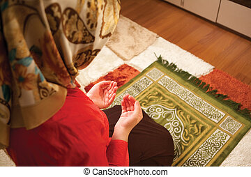 Muslim woman praying - Muslim woman is praying in the house...