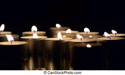 Lots of candles burning in the dark. .