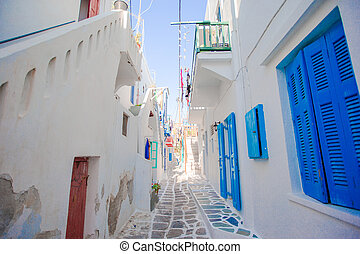The narrow streets of greek island with blue balconies, stairs and flowers. Beautiful architecture building exterior with cycladic style.