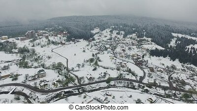 Aerial view. Snow covered village on a hilly terrain
