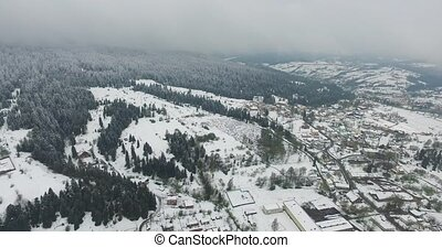 Panoramic shot of a small village on the hillside, snowy...