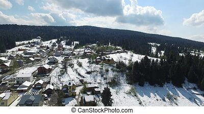 Winter. Village on a hill in the woods. Aerial view - Flying...
