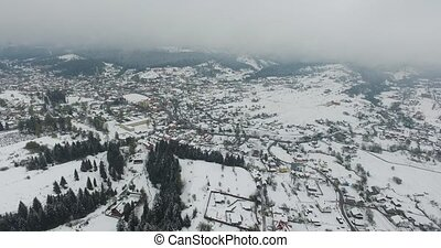 Winter. Flying over the village in the hills of valley