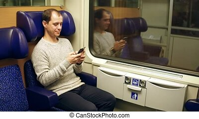 Happy man typing messages in his smartphone in a train....