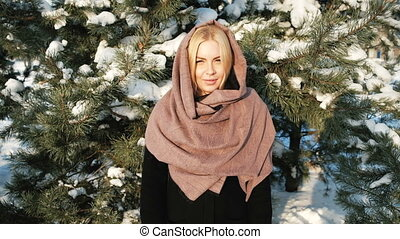 Pleasant woman mistrustfully looks in camera, winter landscape.