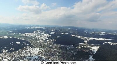 Aerial view. High over snowy rolling hills. Small town