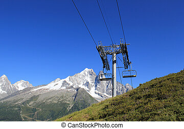Chair lifts  in front of the Mont-Blanc massif, France
